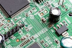 Electronic PCB Printed Circuit Board. In macro close-up with transistors circuitry and electric hardware elements including computer chip with copy space for Stock Photo