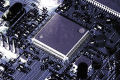 Electronic PCB Printed Circuit Board. In macro close-up with transistors circuitry and electric hardware elements including computer chip with copy space for Royalty Free Stock Photography