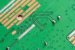 Electronic PCB Printed Circuit Board. In macro close-up with transistors circuitry and electric hardware elements including computer chip with copy space for Stock Photos