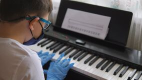 Electronic piano. Fingers press the piano keys. Hands in rubber gloves. Pandemic 2020, self-isolation. Boy in protective gear, mas