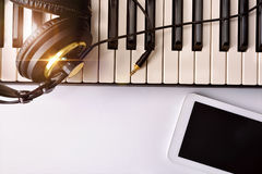 Electronic piano with headphones and tablet for musical composit Royalty Free Stock Images