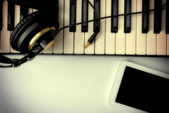 Electronic piano with headphones and tablet for musical composit Royalty Free Stock Photo