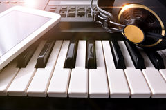 Electronic piano with headphones and tablet in studio front Stock Image