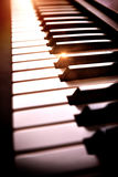 Electronic piano keyboard in the shade with shine elevated view. Close-up of electronic piano keyboard diagonally in twilight with golden shine. Vertical Stock Photo