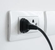Electronic power plug plugged in a wall socket Royalty Free Stock Photo