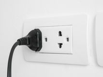 Electronic power plug plugged in a wall socket Royalty Free Stock Image