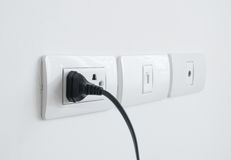 Electronic power plug plugged in a wall socket Stock Photos
