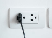 Electronic power plug plugged in a wall socket Royalty Free Stock Photos