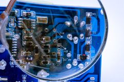 Electronic printed circuit board with soldered cable. View through a magnifying glass. royalty free stock image