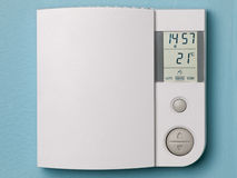 Electronic programmable thermostat. On blue wall Stock Photos
