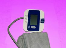 Electronic sphygmomanometer for measuring blood pressure. On a purple background Royalty Free Stock Photo
