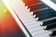 Electronic synthesizer piano keyboard in the sun`s rays macro. Colored rays of light hi-tech stock photography