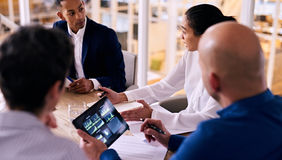 Electronic tablet being used at business meeting in conference room. Group of four business people talking to each other during a business meeting with a Royalty Free Stock Photography