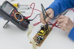 Electronic technician checks the fuse of the power supply royalty free stock images