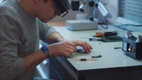 Electronic technician disassemble the smartphone for parts. Put aside the necessary details. At the laboratory table there is a special tool, screwdrivers stock footage