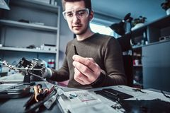Electronic technician mending a broken phone, looking closely at the little bolt holding it with tweezers. In the repair shop stock photo