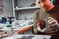 Electronic technician showing a smartphone with a broken body in a repair shop. Electronic technician showing a modern smartphone with a broken body in a repair royalty free stock photography