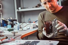 Electronic technician showing a smartphone with a broken body in a repair shop. Electronic technician showing a modern smartphone with a broken body in a repair royalty free stock image