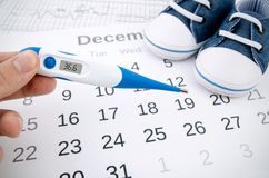 Electronic thermometer in fertility concept. On calendar royalty free stock image