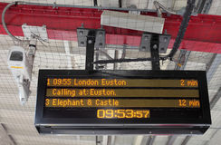 Electronic Timetable on London Railway Platform. Destination and times of trains on London railway station platform electronic timetable with security camera Royalty Free Stock Photo