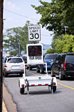 Electronic traffic monitor showing speed limit. Speed Limit Monitor- police speed limit monitor trailer sitting in parking lane of busy street Royalty Free Stock Image