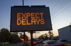 Free Electronic Traffic Sign Stating Expect Delays With Blurred Traffic At Sunset Royalty Free Stock Photo - 176985025