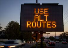 Free Electronic Traffic Sign Stating Use Alternate Routes With Blurred Traffic Stock Photos - 176984933