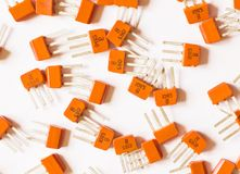 Electronic transistors. Electronic transistors of orange color lie on a light background Royalty Free Stock Images
