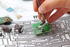 Electronics components. A hand hand with tweezers holding a electronic circuit board on the background of electronic scheme royalty free stock images