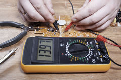 Electronics engineer. Brush an electronics engineer close-up. Electrician man making measurements on electronic board Stock Image