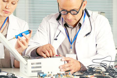 Electronics engineer. Scientist working with electronic transistor at the laboratory with his female assistant Stock Photography