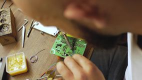 An electronics engineer solders an electrical board with processors. Master repairs electrical equipment. view from above. 4 k vid. Eo stock video