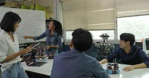 Electronics engineer team meeting, collaborating on construction of robot in the workshop.