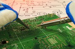 Electronics manufacturing services, manual soldering of electronic board. From spare parts stock image