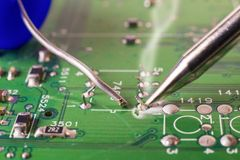 Electronics manufacturing services, soldering of electronic board. Close-up royalty free stock photography