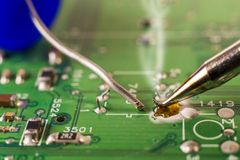 Electronics manufacturing services, soldering of electronic board stock photos