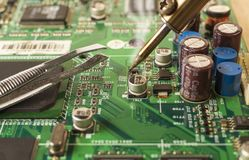 Electronics manufacturing services, soldering of electronic board. Close up view royalty free stock photos