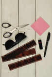 Electronics, photo & stationery with sunglasses the wood on the table. On a light wooden table photo film , paper pink unit stickers, flashcards black, pen with Royalty Free Stock Photo