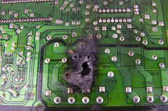 Electronics repair - burned out board to black hole stock image