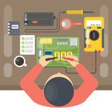Electronics repair man. Electronics repair man sitting at the table with tools. Top view Royalty Free Stock Image