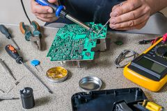Electronics repair and metering. Parameters. Broken electronic board, professional repairman Stock Image