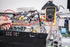 Electronics Repair. Service with red probe and capacitors on electronic board Stock Image