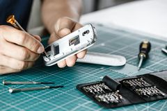 Electronics repair service. Technician disassembling smartphone for inspecting royalty free stock photo