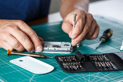 Electronics repair service. Technician disassembling smartphone for inspecting. Royalty Free Stock Photos