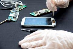 Electronics repair service - technician is fixing broken cell phone. Electronics repair service concept - technician is fixing broken cell phone stock photos