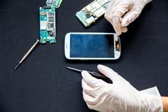 Electronics repair service - technician is fixing broken cell phone stock images