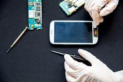 Electronics repair service - technician is fixing broken cell phone. Electronics repair service concept - technician is fixing broken cell phone royalty free stock photos