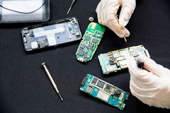 Electronics repair service - technician is fixing broken cell phone. Electronics repair service concept - technician is fixing broken cell phone stock photography