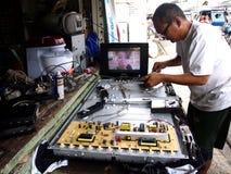 An electronics repair shop technician works on a flat screen tv. Stock Photos