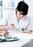 Electronics repair worker reading Royalty Free Stock Photos